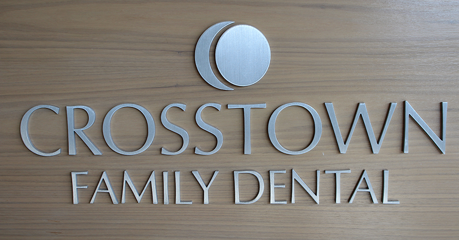 Crosstown Family Dental silver logo against wood at dentist office in Richfield, MN